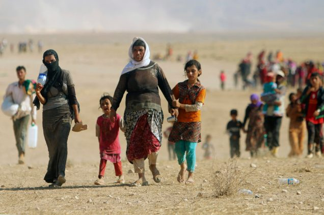 Displaced people from the minority Yazidi sect, fleeing violence from forces loyal to the Islamic State in Sinjar town, walk towards the Syrian border, on the outskirts of Sinjar mountain, near the Syrian border town of Elierbeh of Al-Hasakah Governorate August 11, 2014. Islamic State militants have killed at least 500 members of Iraq's Yazidi ethnic minority during their offensive in the north, Iraq's human rights minister told Reuters on Sunday. The Islamic State, which has declared a caliphate in parts of Iraq and Syria, has prompted tens of thousands of Yazidis and Christians to flee for their lives during their push to within a 30-minute drive of the Kurdish regional capital Arbil. Picture taken August 11, 2014. REUTERS/Rodi Said (IRAQ - Tags: CIVIL UNREST POLITICS SOCIETY)